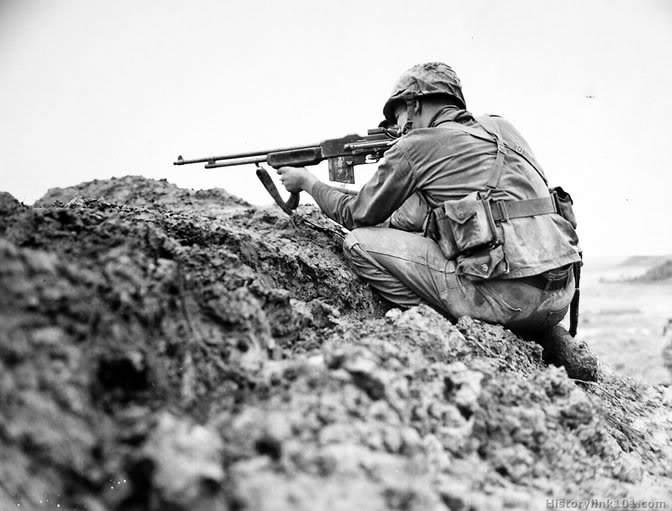 Un soldat fait feu avec son B.A.R 1918 modifié sur le terrain avec l'ajout d'une crosse, à Okinawa