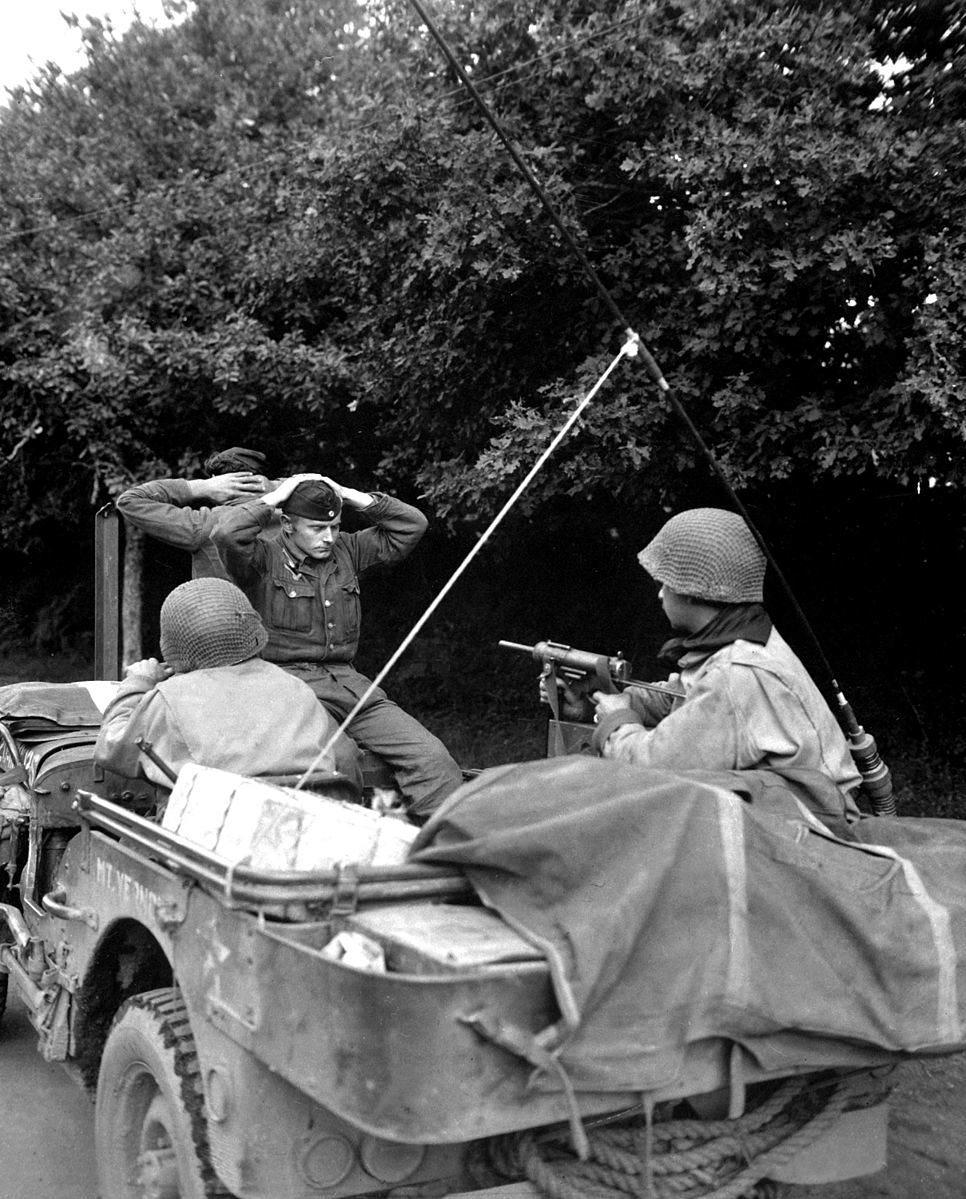 Battle of Brittany   Lorient 01 - A Plouay (nord de Lorient) des soldats de la 6th Division amènent un prisonnier Allemand à un interrogatoire, sous bonne garde d'un M3