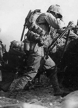 firearms shotgun win12 marine ww2 375 - Le 1er avril 1945, ce marines, présent sur la plage Blue Beach 2 d'Okinawa recharge sa winchester 1912. Il fait partie du 1er bataillon, 7th Marines
