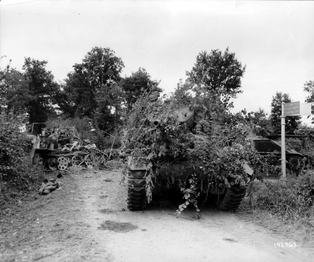 Un char M10 du 703rd TD Battalion avance avec précautions au carrefour de La Bruyère près de Rânes. A gauche, un SdKfz 7 avec un canon de Flak de 88mm détruit, avec le corps d'un de ses membres d'équipage au sol. A droite, un sherman M4 détruit.