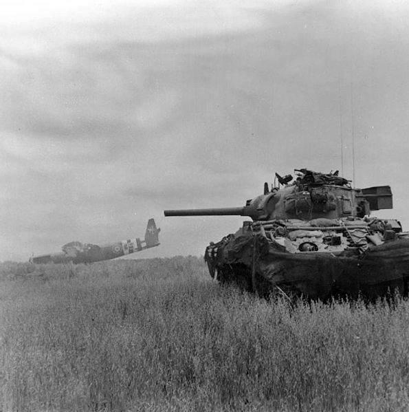 595px Sherman tank and Horsa glider - Un sherman en action près de Ranville, le 10 août 1944. Il utilise un planeur Horsa comme couverture.