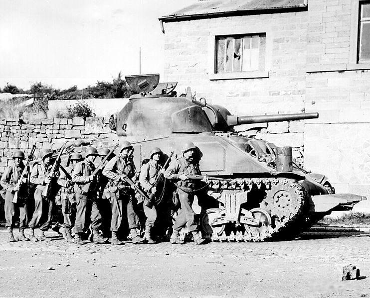 742px Yanks advance into a Belgian town - Des soldats du 60th Infantry Regiment avancent à couvert d'un Sherman des les rue d'une ville en Belgique