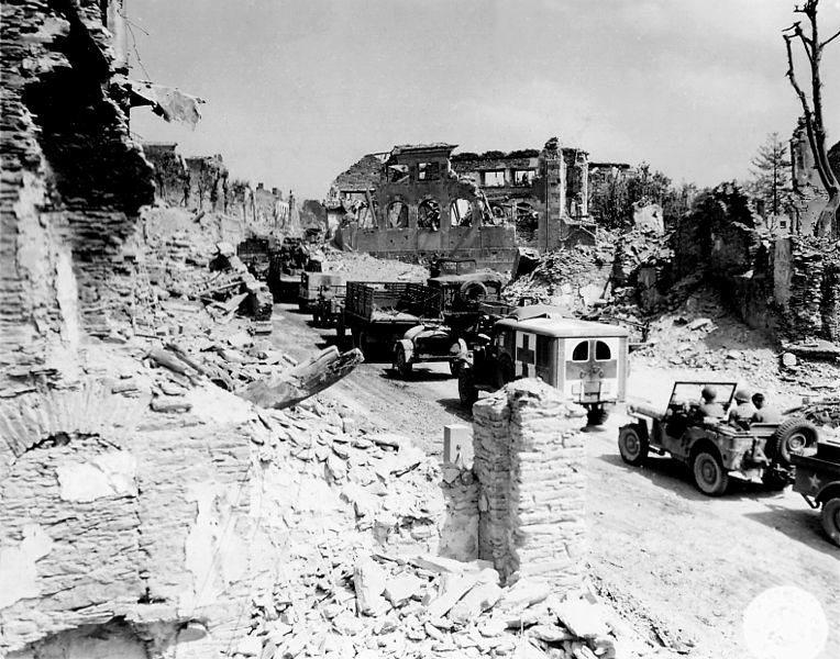 764px Military convoy through Saint Lo - Une ambulance traverse les rues dévastées de Saint-Lo, en juin 1944