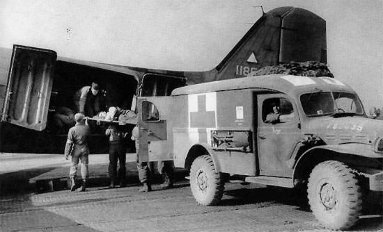 wc 54 1 - Un Dodge WC-54 du 61st Med Bn, 5th E.S.B. débarque ses patients dans un C-47, qui seront renvoyés vers des hôpitaux en Angleterre.