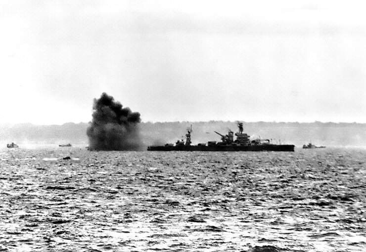 USS Arkansas (BB 33) fires her guns at German positions - Le navire de classe Arkansas (BB33), faisant feu sur les batterie Allemandes avec ses canons de 12-inch le 6 juin 1944