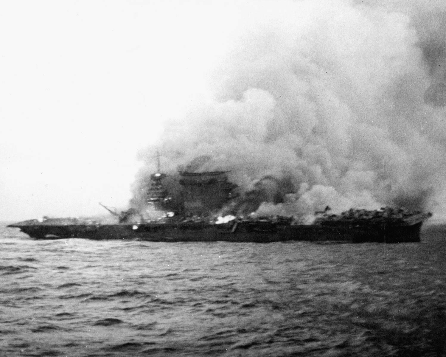 USS Lexington brennt - Le USS Lexington brûle et coule. Photo prise peu de temps après que son personnel de bord ait quitté le navire. On peut encore voir des avions en queue de navire, qui n'ont pas été touchés