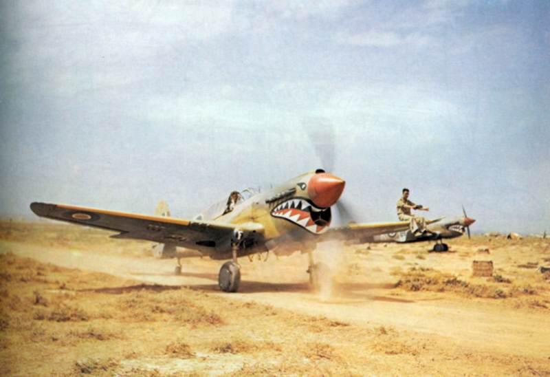TR 000978 kittyhawk - Un Warhawk Mk III du 112 Squadron de la RAF, s'avançant sur la piste à Medenine (Tunisie) en 1943. Un membre au sol est assis sur l'aile afin de diriger le pilote, qui ne pouvait pas voir la piste à cause du nez relevé.