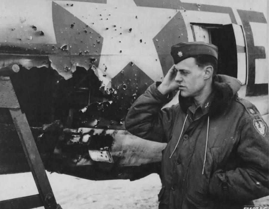 5f03fe0896226d64a9d18a173eebda61 - Le Major Loren W Herway examine un P-47 touché par un canon de 88. Il aura tout de même dû atterrir sur le ventre