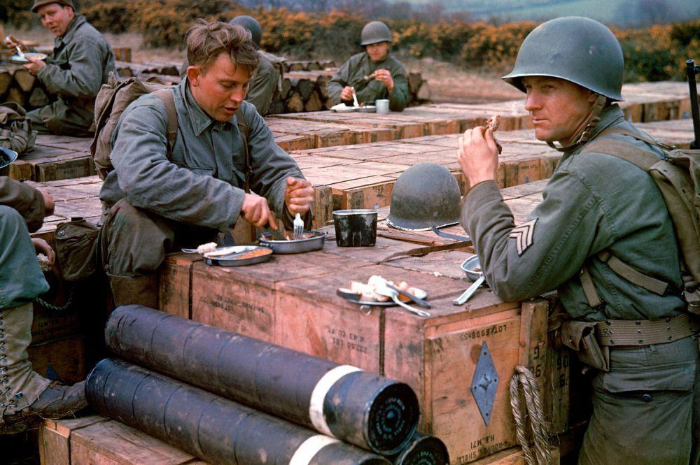d day color 02 - Des ingénieurs cassent la croûte sur des caisses de munitions, prêtes pour le DDAY en mai 1944