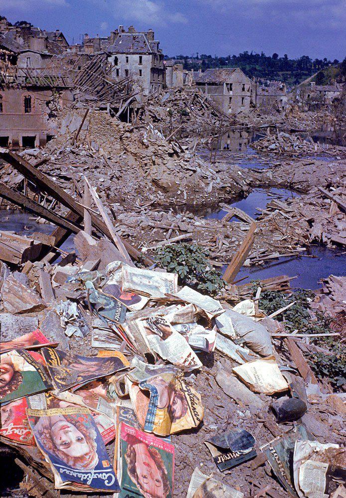 d day color 08 - Des magazines éparpillés au dessus des débris de la ville de Saint-Lô en juin 1944