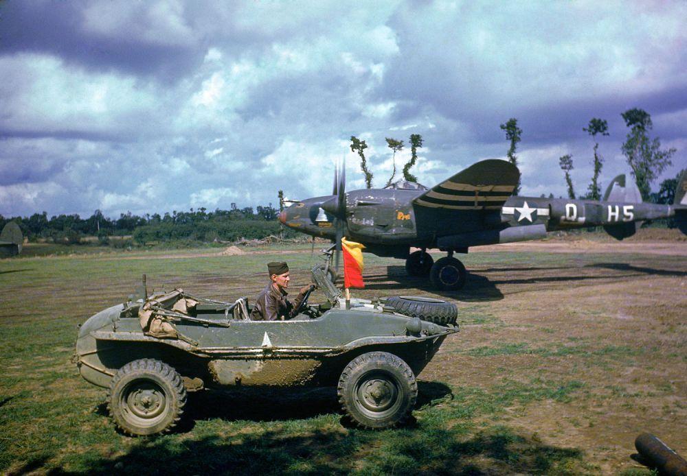 d day color 17 - Un soldat roulant dans une voiture Allemande capturée passe devant un P-38 Lightning