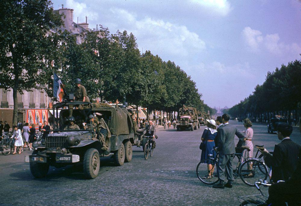 d day color 19 - Des camions américains (plus un cycliste civil accroché au premier plan) paradent sur les champs Elysées juste après la libération de Paris, en août 1944