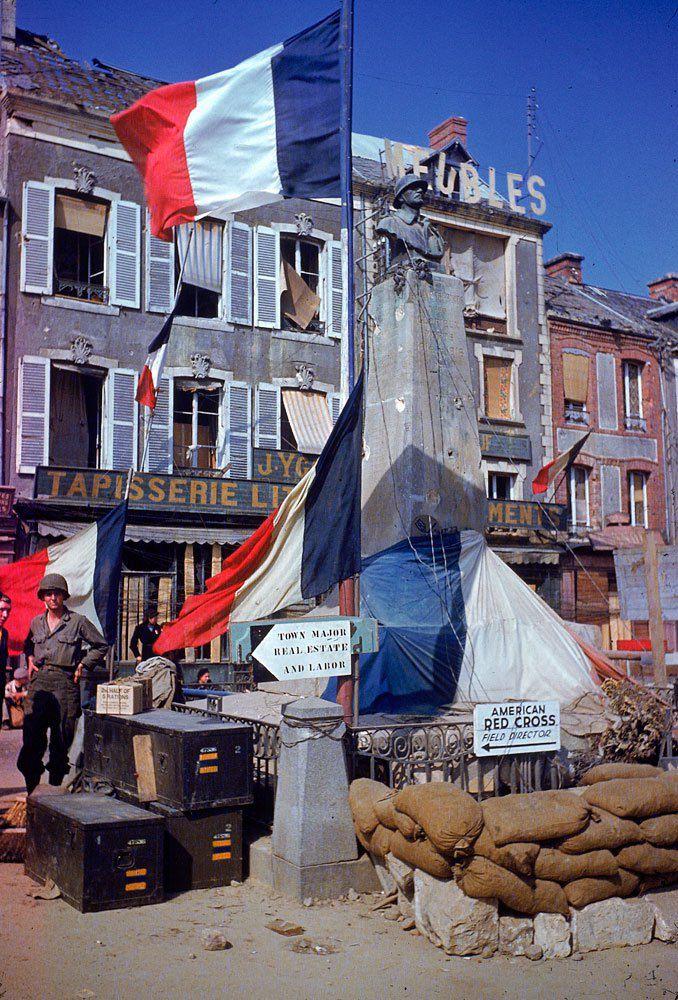 d day color 25 - Des troupes américaines en repos près d'un monument au mort de la première guerre mondiale en été 1944. Lieu exact inconnu.