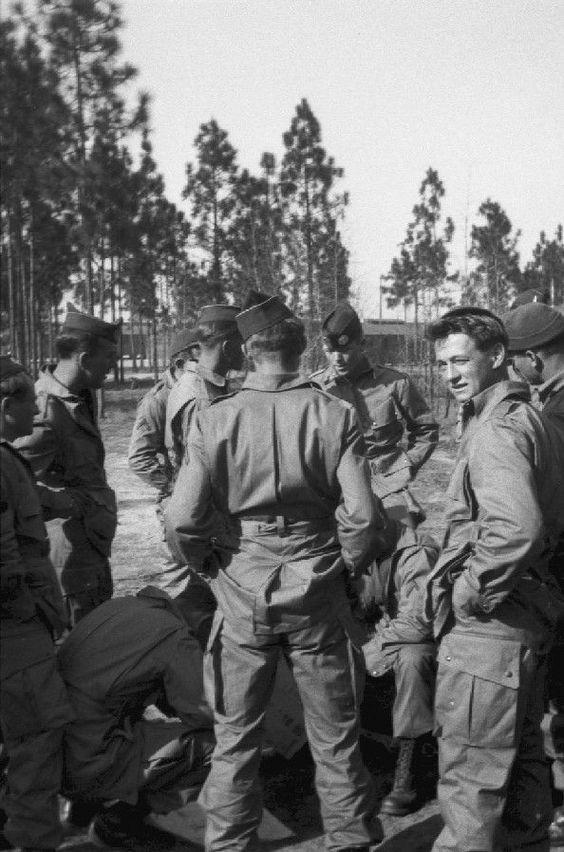 dcdf10cb595a25e6889fedbcc2f7c33e - Richard Winters (au fond face de face) apprenant à ses hommes comment plier son parachute. Skip Muck est à droite et regarde l'appareil photo..