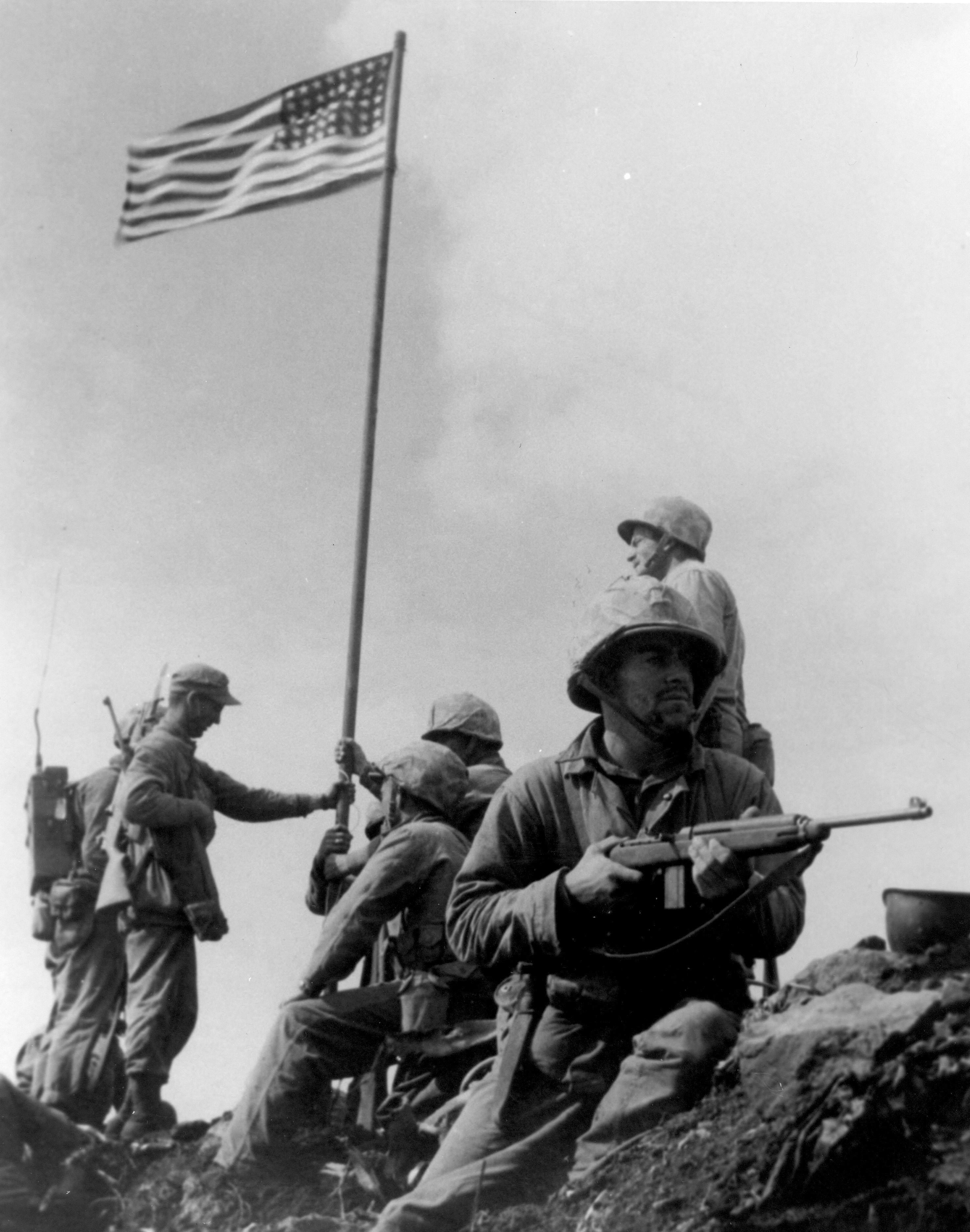 First Iwo Jima Flag Raising - Le drapeau américain est hissé à Iwo Jima, sous l'oeil d'un GI portant une carabine M1