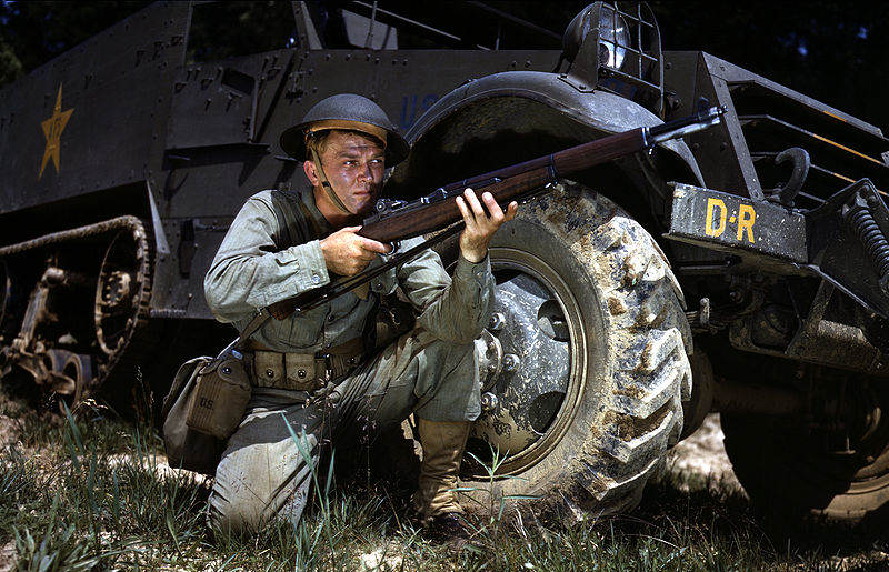 800px Infantryman in 1942 with M1 Garand, Fort Knox, KY - Juin 1942 : Accroupi près d'un M3 Half-track, ce soldat pose avec son M1 Garand à Fort Knox