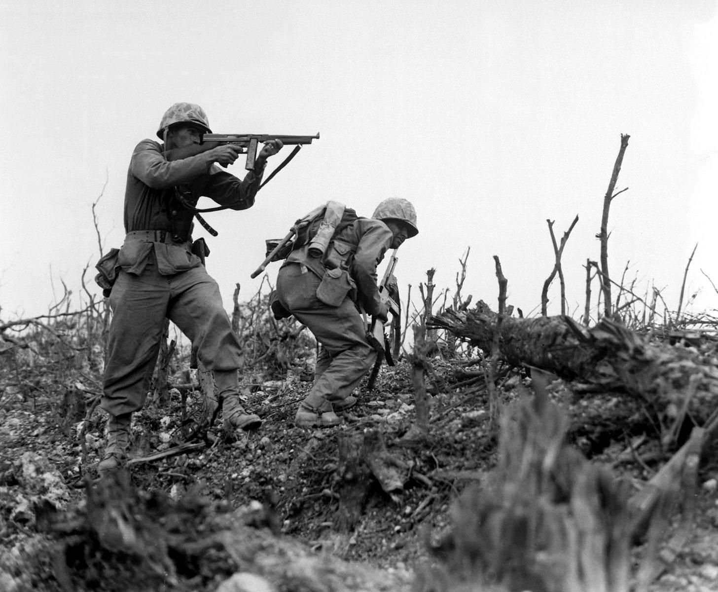 USMC Okinawa Thompson - n Marines de la 1st Marine Division couvre un de ses camarades  pour débusquer une sniper sur l'île d'Okinawa en 1945.