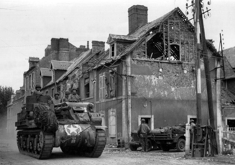 800px American tank in Carentan - Un M7 Priest traverse Carentan en juin 1944