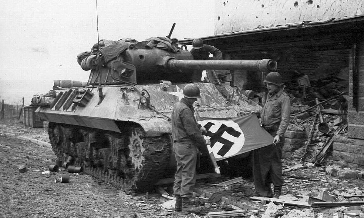 M36 1944 - Des soldats américains ont trouvé un drapeau nazi. Derrière eux, un M36 Jackson