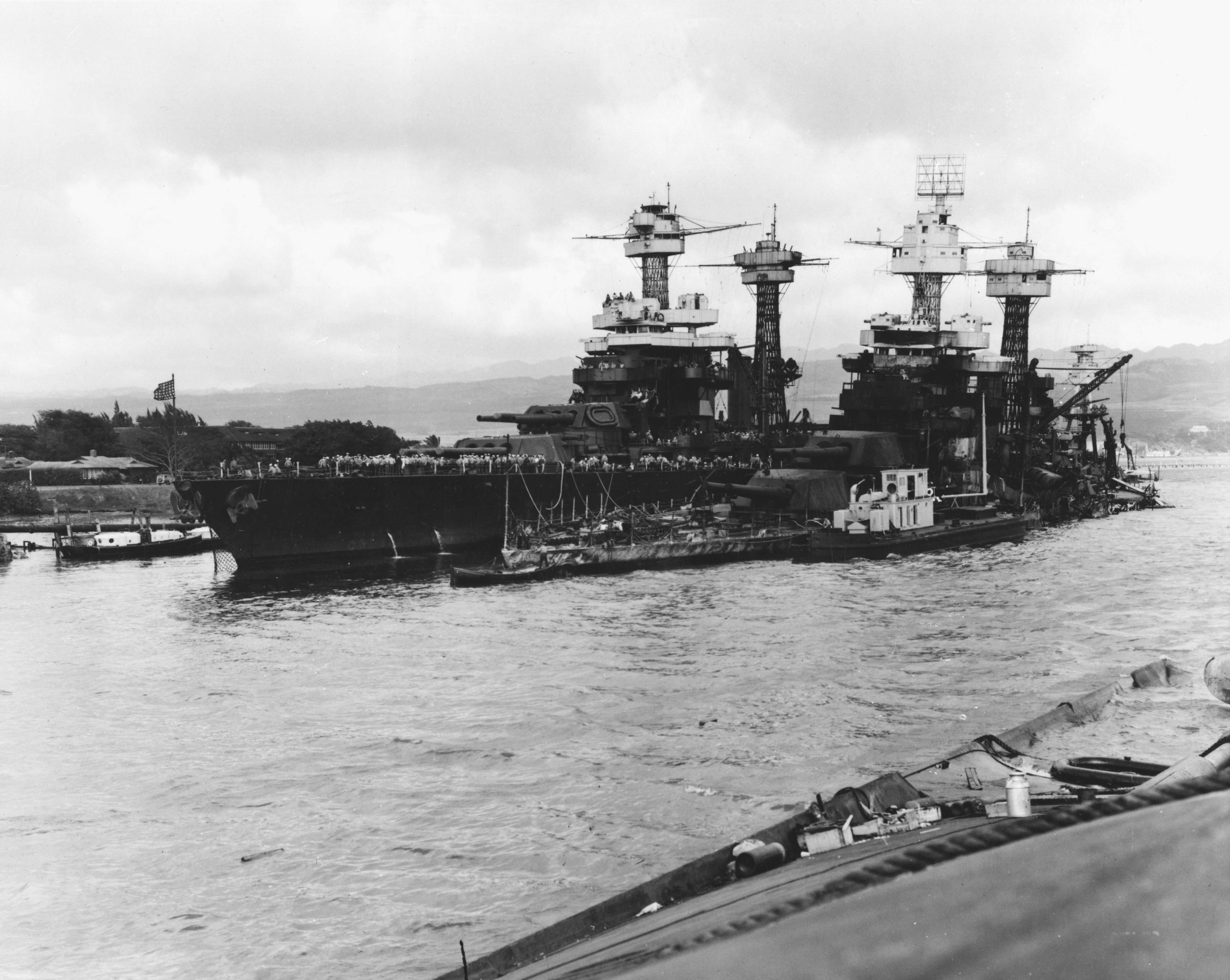 Pearlharbour bb48 bb43 - Le USS Tennessee endommagé par l'attaque de Pearl Harbor (à gauche). Il se trouve à côté de l'USS West Virginia (BB-48) qui a coulé. Photo prise depuis le USS Oklahoma (BB-37) le 10 décembre 1941