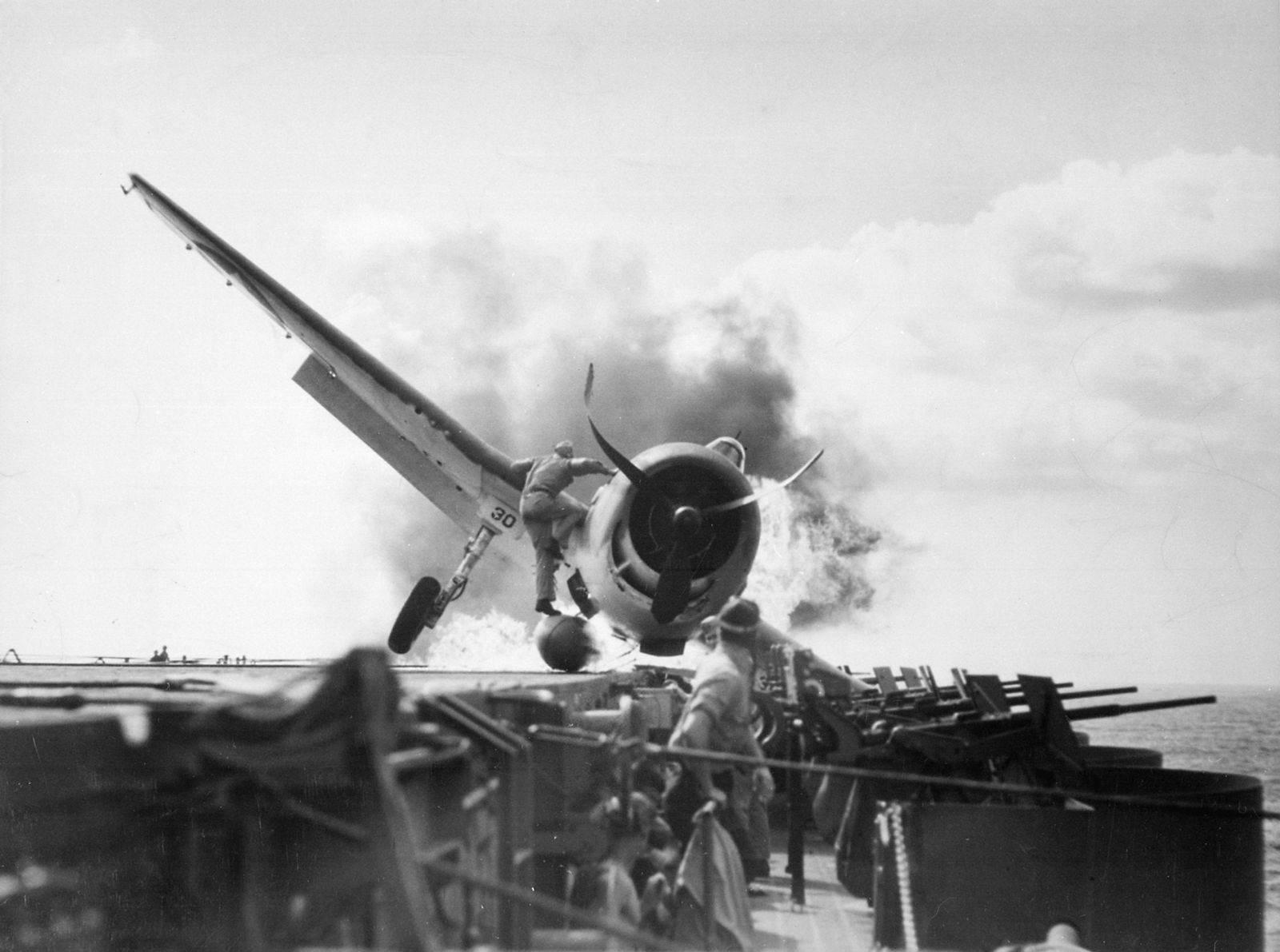 EnterpriseBurningHellcat - Un F6F-3 en feu sur le USS Enterprise le 10 novembre 1943. Le Lt. Walter L. Chewning, Jr monte sur l'avion pour aider le pilote à sortir de son avion en feu. Il s'en tirera sans grande blessure